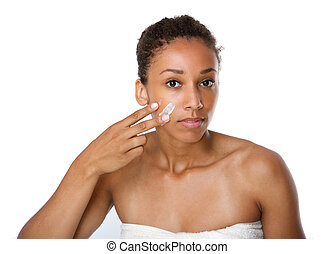 Young woman applying beauty cream on face