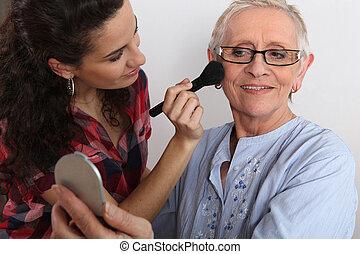 Young woman applying blush on her grandmother's cheeks