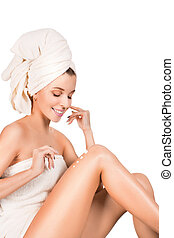Young woman applying body lotion over white background.