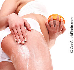 Young woman applying cosmetic cream on leg.