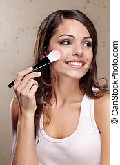 Young woman applying cosmetic paint brush