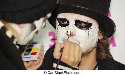 Young Woman Applying Dark Makeup Onto Man's Face At Halloween