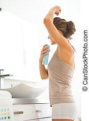 Young woman applying deodorant on underarm