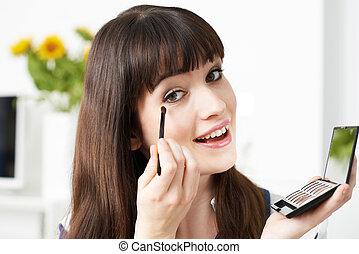 Young Woman Applying Eye Make Up At Home
