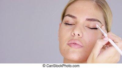 Young woman applying eye makeup to her eyelid - Young woman...