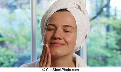 Young pretty woman with a towel turban on her head applying facial moisturizer