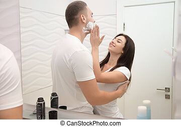 Young woman applying gently foam for a man to shave