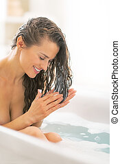 Young woman applying hair conditioner in bathtub