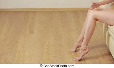 Young woman applying legs cream concept. joint pain. warming gel