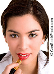 A beautiful young brunette is applying lipstick