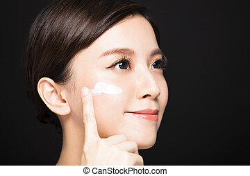 young woman applying lotion cream on face