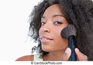 Young woman applying make-up while using a powder brush...