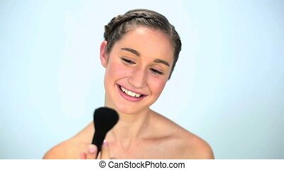 Young woman applying make up - Young woman applying brush...