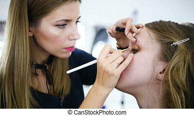 Young woman applying makeup to model in salon - Shot in 4k...