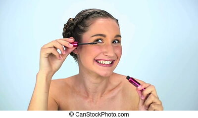 Young woman applying mascara on her eyelash on white...