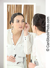 Young woman applying mascara in front of a bathroom mirror