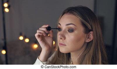 Young woman applying mascara looking at mirror. Slow motion