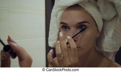 Young woman applying mascara on eyelashes in the bathroom. -...