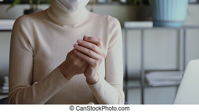 Young woman applying sanitizer gel rubbing hands before distance computer work from home office on remote quarantine. Female worker wearing mask using sanitiser for corona virus protection concept.