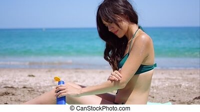 Young woman applying sun cream to her legs as she sits sunbathing on a towel on a tropical beach in summer sun