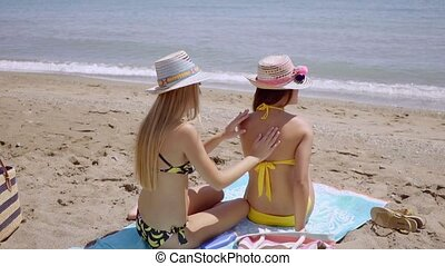 Young woman applying sunscreen on a friend
