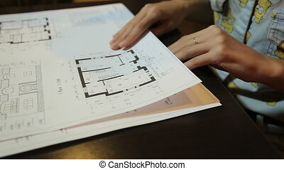 young woman architect chooses the blueprint sheets with layouts and drawings of the premises.