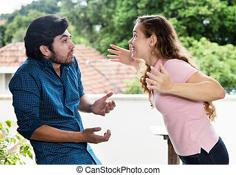 Young woman arguing with latin american friend outdoors