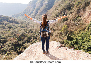 young woman arms open on mountain cliff