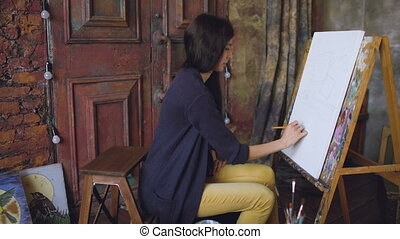 Young woman artist draw scetch wit pencil on easel canvas,...