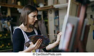 Young woman artist in apron painting picture on canvas in...