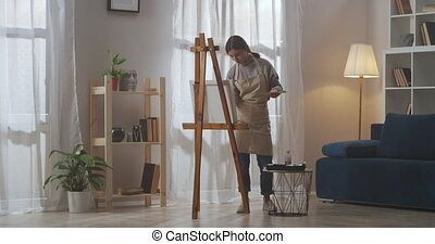 young woman artist is using living room of apartment as artistic workshop for drawing, hobby and professional skills, painting by oil colors