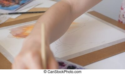 Young woman artist painting at home studio creative tools close-up