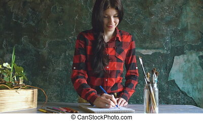 Young woman artist painting scetch on paper notebook with pencil and smile