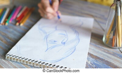 Young woman artist painting scetch on paper notebook with pencil closeup
