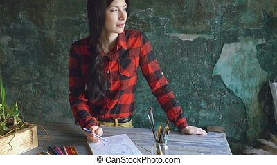 Young woman artist painting scetch on paper notebook with pencil looks in window