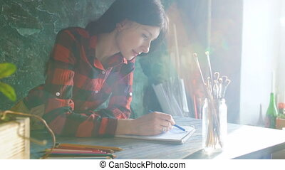 Young woman artist painting scetch on paper notebook with pencil. Bright sun flare from window
