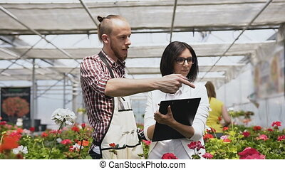 Young woman as customer shopping in florist shop, buying flowers for gardening. People in flower shop, client pushing cart. Buyer talking to sales gardener in greenhouse.