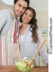 Young woman Asian and man preparing meal in kitchen