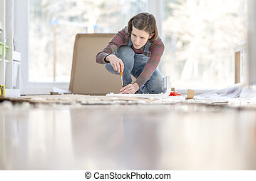 Young Woman assembling a DIY furniture at home kneeling on the floor in front of a bright glass window