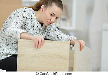 young woman assembling the parts of the furniture