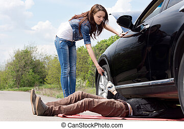 Young woman assisting a mechanic on her car