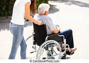 Woman Assisting Her Disabled Father On Wheelchair