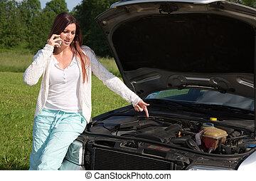 Young woman at a broken down car