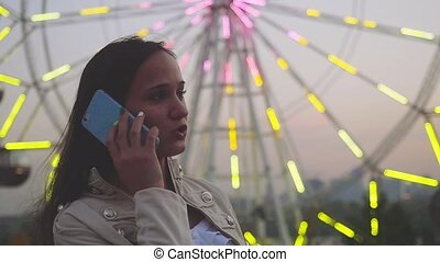 Young woman at an attractions park arcade talk by smartphone...