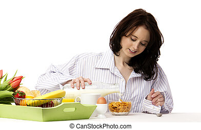 young woman at breakfast pouring milk in corn flakes