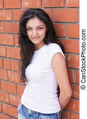 Young woman at brick wall