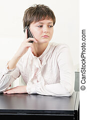 Young woman at desk with phone
