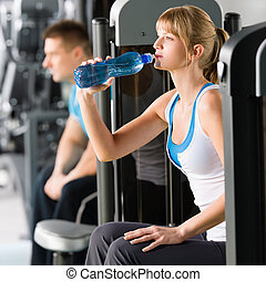 Young woman at gym drink water