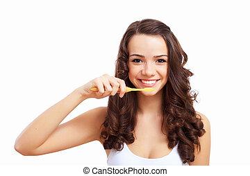 Young woman at home brushing teeth