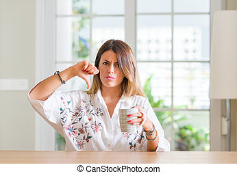 Young woman at home drinking coffee with angry face, negative sign showing dislike with thumbs down, rejection concept